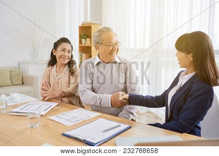 Smiling Senior Man Shaking Hand Of Pretty Young Realtor After Signing Real Estate Purchase Agreement
