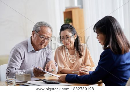 Loving Senior Couple Sitting At Spacious Office Of Estate Agent And Asking Questions Concerning Term
