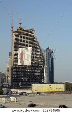 Doha, Qatar - March 21, 2018: skyscraper under construction in Qatar with a 12-storey high poster of Emir Tamim displayed on it.