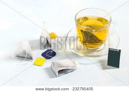 Several Tea Bags Of Different Shapes And With Different Kinds Of Tea And Cup Of Tea On Light Blue Ba