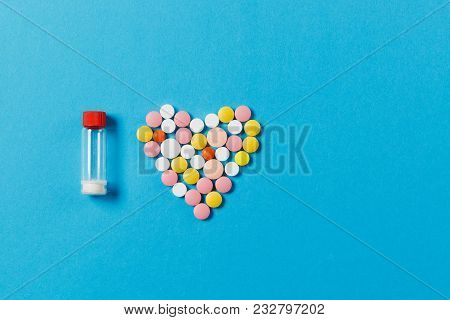 Medication White, Colorful Round Tablets In Form Of Heart Isolated On Blue Background. Bottle With P