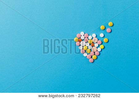 Medication Colorful Round Tablets In Form Of Diffusion Heart Isolated On Blue Background. Pills Shap