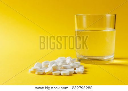 Medication Pile White Round Tablets Arranged Abstract On Yellow Color Background. Aspirin, Glass Wat