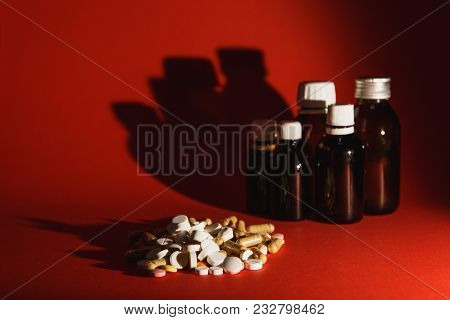 Medication White Colorful Tablets Arranged Abstract On Dark Red Color Background. Aspirin, Vial, Bot