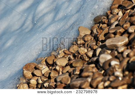 Close-up Of Sunlit Brown Pebble Stones And Bluish Foamy Water On A Riverbed
