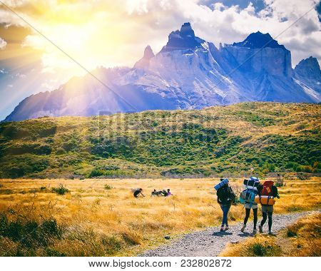 Group Of Travelers With Backpacks Walk Along A Trail Towards A Mountain Ridge.backpackers Style. Con