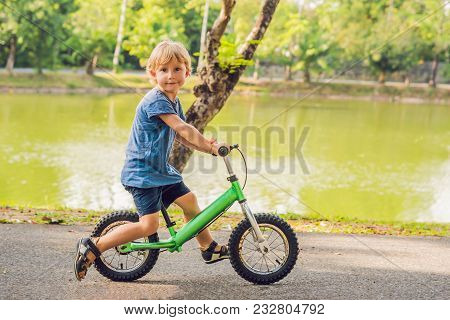 Little Boy On A Bicycle. Caught In Motion, On A Driveway. Preschool Child's First Day On The Bike. T