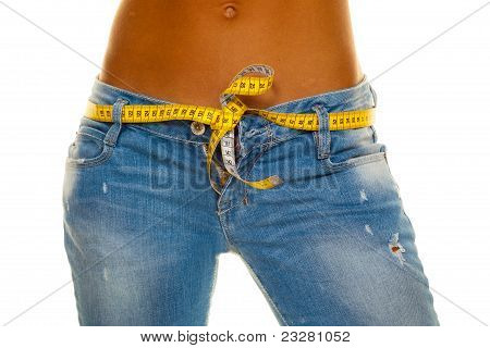 Slim woman in jeans with tape measure
