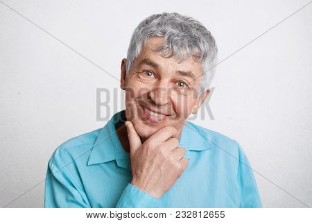 People, Pension And Positive Emotions Concept. Pleased Mature Male With Grey Hair, Keeps Hand Under