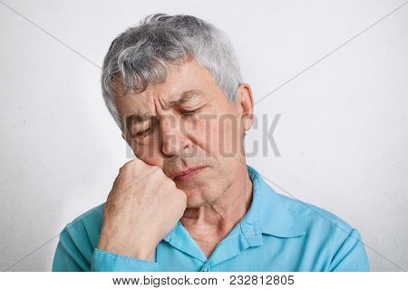 Thoughtful Elderly Male With Pensive Expression, Feels Lonely, Keeps Hand Under Chin And Contemplate