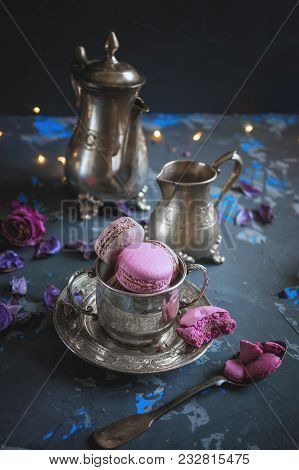 Freshly Baked Macaroons On A Silver Metal Cup With Bokeh From The Lights On The Wooden Background. S