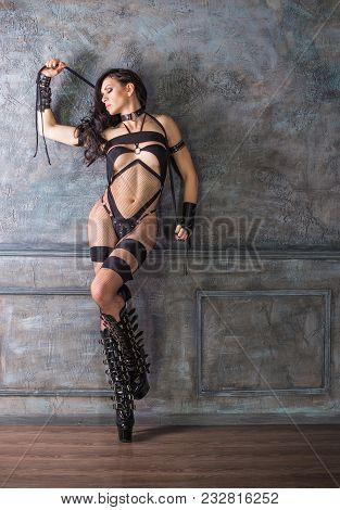 Full Length Portrait Of A Woman Wearing A Black Sexy Gothic Outfit. Standing Pose, Against A Dark Wa