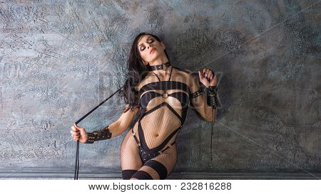 Young Woman In Sexual Dominatrix Black Leather Lingerie With A Whip In Her Hand. Dominating A Slave