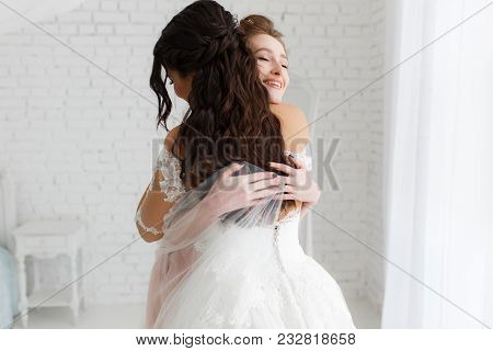 Luxury Bride Hugging Bridesmaid And Smiling, Joyful Moment In Minimalistic Loft White Brick Backgrou