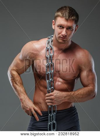 Musculed Bodybuilder Showing His Body Holding Steel Chain