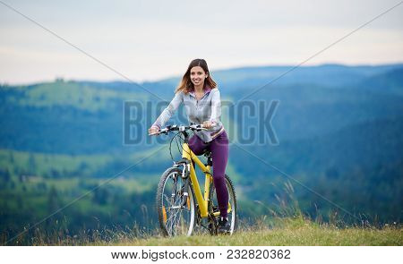 Strong Female Biker Cycling On Yellow Mountain Bike On A Rural Trail In The Evening. Mountains On Th