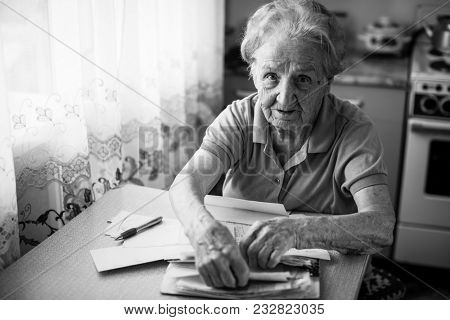 Elderly woman pensioner with bills to pay utilities.