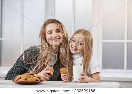Close Up Of Two Smiling Sisters-younger And Oder. Both Girls Have Blonde Straight Hair. They Are Eat