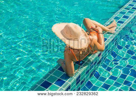 Beautiful tanned woman in swimwear relaxing in swimming pool spa.