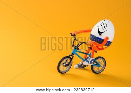 Funny Easter Egg Sitting On A Miniature Bicycle. Space For Text.