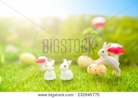 Happy Easter Concept. Easter Rabbits Toy On Spring Green Grass. Fairy Tale Sunset On The Plastic Gre