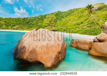 Beautifully shaped granite boulders in the turquoise sea  and a perfect white sand at Anse Coco, La Digue island, Seychelles.