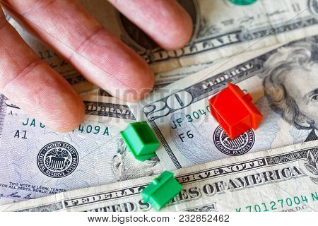 Overturned Miniature Houses And A Hand On Top Of American Usd Dollar Currency Symbolising Expensive