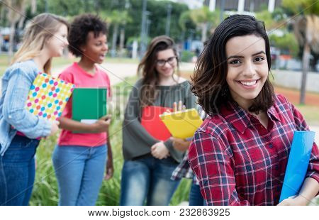 Hispanic Female Student With Group Of International Students Outdoors On Campus Of University