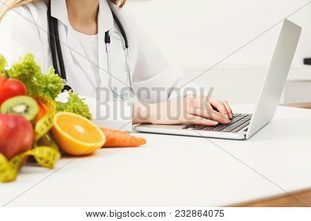 Female Nutritionist Working On Laptop In Office, Close Up. Hands Of Woman Dietitian Typing, Counting