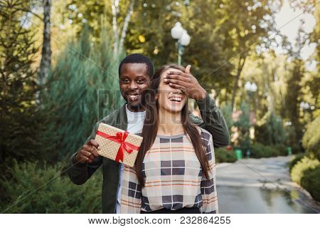 Young African-american Man With Giftbox Closing His Girlfriend Eyes To Make Surprise For Her, Walkin
