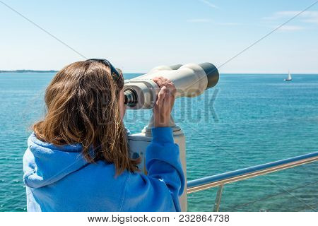 Woman Looking Through Coin Operated Binoculars At Seaside. Tourist Exploring New Country.