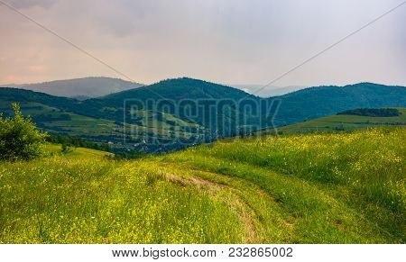 Country Road Through Rural Field. Lovely Mountainous Landscape On An Overcast Day