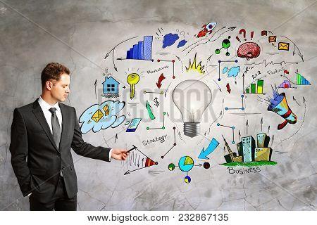 Presentation And Idea Concept. Portrait Of Handsome European Businessman Standing On Concrete Wall B
