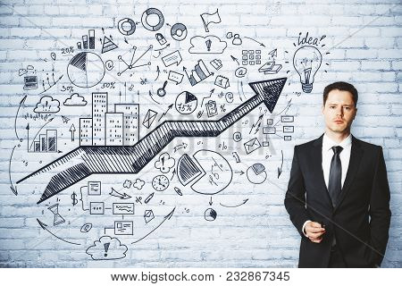 Presentation And Success Concept. Portrait Of Handsome European Businessman Standing On Brick Wall B