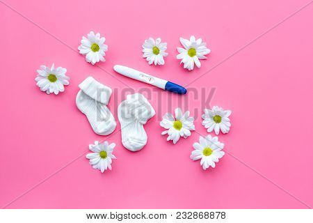Joy of long-awaited pregnancy. Pregnancy test with two stripes near flowers on pink background top view mock-up. poster