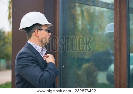 Manager Wears Smart Suit, Tie And Hardhat And Watch At Glass Mirror. Architect Controls Work. Man Wi