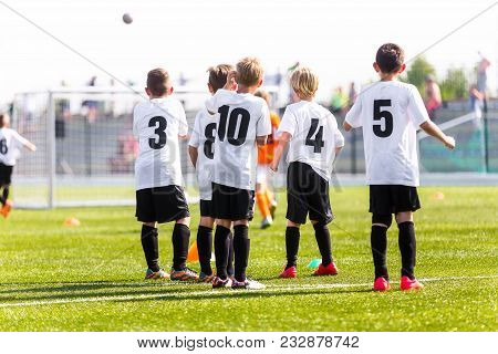 Kids Football Team. Young Boys Watching Soccer Match. Football Tournament Competition In The Backgro