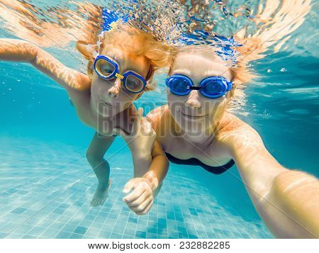 Mom And Son In Diving Glasses Swim In The Pool Under The Water.