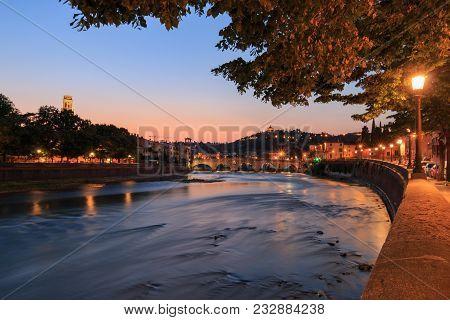 Panoramic View To Bridge Ponte Pietra In Verona On Adige River, Veneto Region, Italy On A Warm Eveni