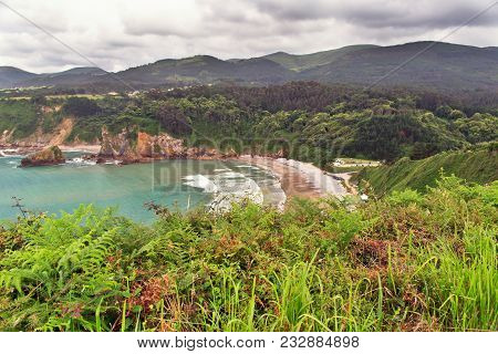 View Of A Sea Bay With Steep Coast. The Cloudy Sky With Clouds, A Bright Green Grass And Hills In Th