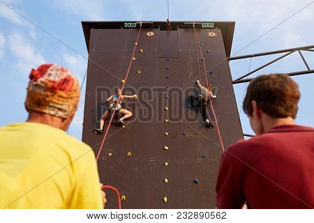Bottom View Of Two Young Women Climbers Insured By Men On Rope Belay Harness Approaching To Finishin
