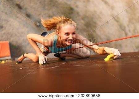 Strong Woman And Business Success Concept. Young Caucasian Strong Woman Practicing Climbing On Artif