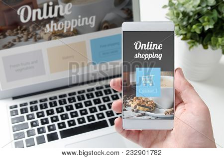 Online Shopping Concept On Smart Phone And Laptop. Hand Holding Mobile Phone.