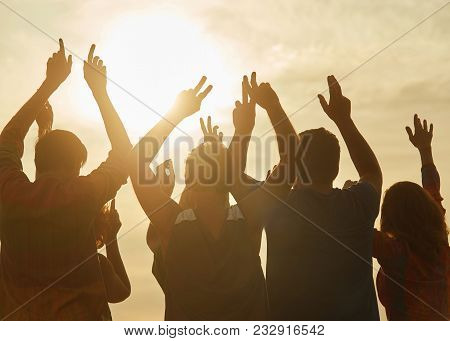 People Celebrating Victory, Hands Up. Back View. Evening Sun Background.