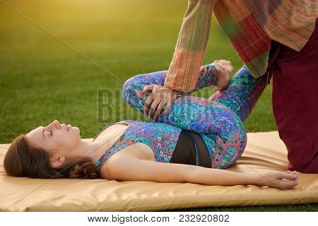 Gymnastic Thai Massage Yoga Exercise. Close Up Lying Woman Getting Thai Massage On Mat Outdoor.