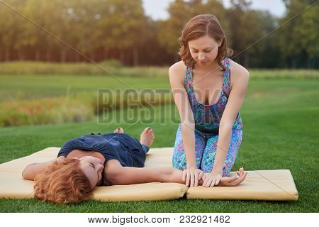 Massaging Arm Outdoor. Thai Yoga Arm Massage On Mat In The Park.