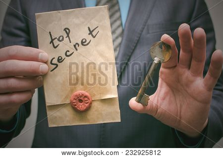 Top Secret Concept. Top Secret Documents Or Message And A Decryption Key In Businessman Hands. The K