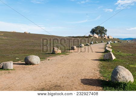 Boulder-lined Trail Leading To A Mountain Range In The Distance At Ramona Grasslands Preserve In San