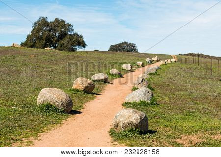 A Dirt Trail Lined With Boulders At Ramona Grasslands Preserve In San Diego County.