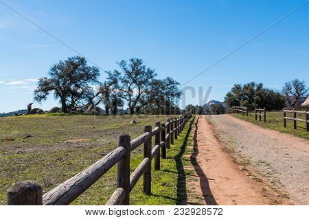 A Wooden Fence Along A Dirt Road Leading To A Copse Of Trees At Ramona Grasslands Preserve In San Di